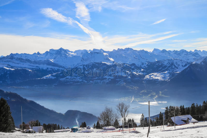 Panoramic skyline view of snow-capped chalets and. Mountains over foggy Vierwaldstattersee, and snow covered Rigi, Lake Lucerne, Switzerland stock image