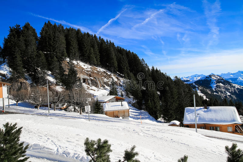 Panoramic skyline view of snow-capped chalets and. Mountains over foggy Vierwaldstattersee, snow covered Rigi, Lake Lucerne, Switzerland royalty free stock images