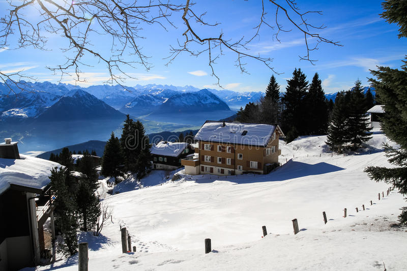 Panoramic skyline view of snow-capped chalets. And mountains over foggy Vierwaldstattersee, snow covered Rigi, Lake Lucerne, Switzerland royalty free stock photography