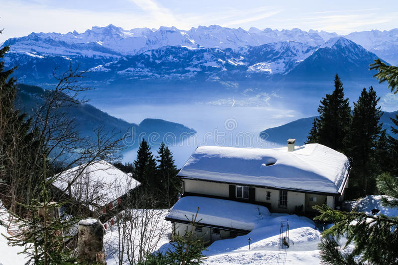 Panoramic skyline view of snow-capped chalets. And mountains over foggy Vierwaldstattersee, snow covered Rigi, Lake Lucerne, Switzerland royalty free stock photo