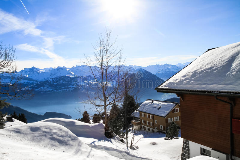 Panoramic skyline view of snow-capped chalets and. Mountains over foggy Vierwaldstattersee, Rigi, Lake Lucerne, Switzerland royalty free stock photo