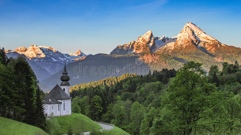 Panoramic view of Maria Gern church with snow-capped summit of Watzmann mountain stock images