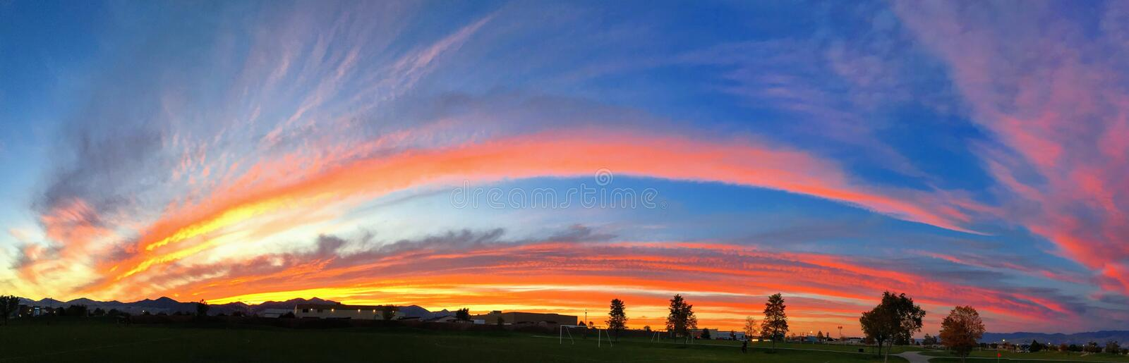 Panoramic striking sunset background with vivid orange, blue, red and yellow, in the shape of a rainbow. royalty free stock image