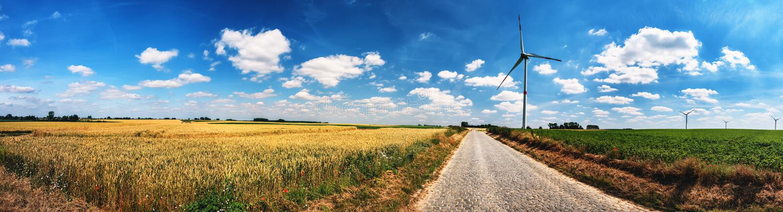 Panoramic summer landscape with country road and wind turbines stock images