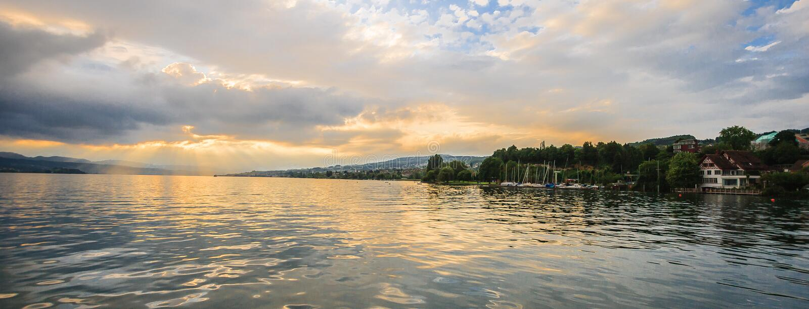 Panoramic summer view of boat cruise excursion landscape on Zurichsee with beautiful sunset shining light through clouds reflected royalty free stock photography
