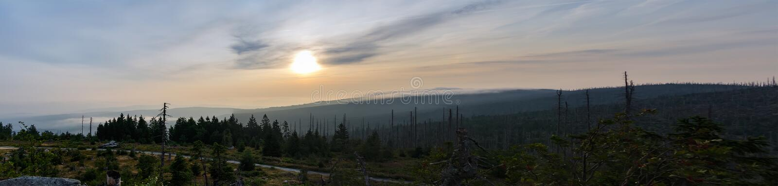 Panoramic sunrise with trees, distant hill and fog on Tristolicnik. Sumava National Park and Bavarian Forest, Czech republic and royalty free stock images