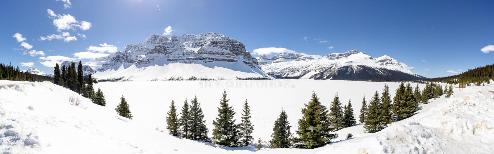 Panoramic View of Alpine Mountains over Frozen Lake. Panoramic view of alpine mountain over frozen lake off of glacier parkway in banff national park stock photos