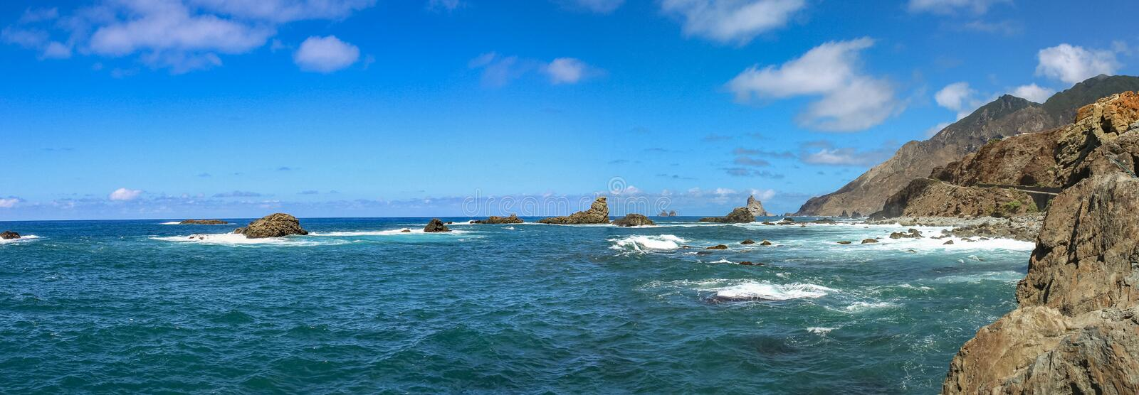 Panoramic view of Anaga cliffs and lone rocks sticking out of the sea foam on the north coast of the island Tenerife, Spain stock photo