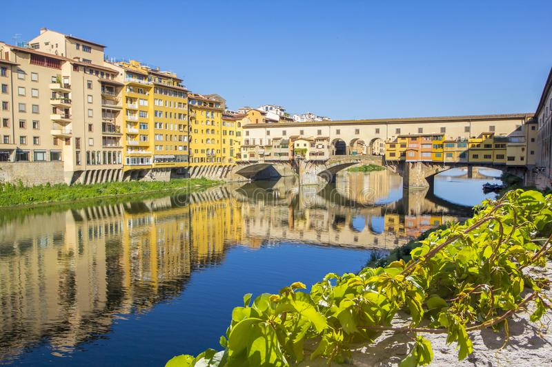Panoramic view of the Arno River and stone medieval bridge Ponte Vecchio with beautiful reflection of colorful houses, Florence royalty free stock photos