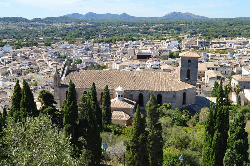 Church and panoramic view of Arta Mallorca. Panoramic view of of Arta Mallorca, Spain, the coast and the hills, the almond orchards, olive groves and the Torre royalty free stock image