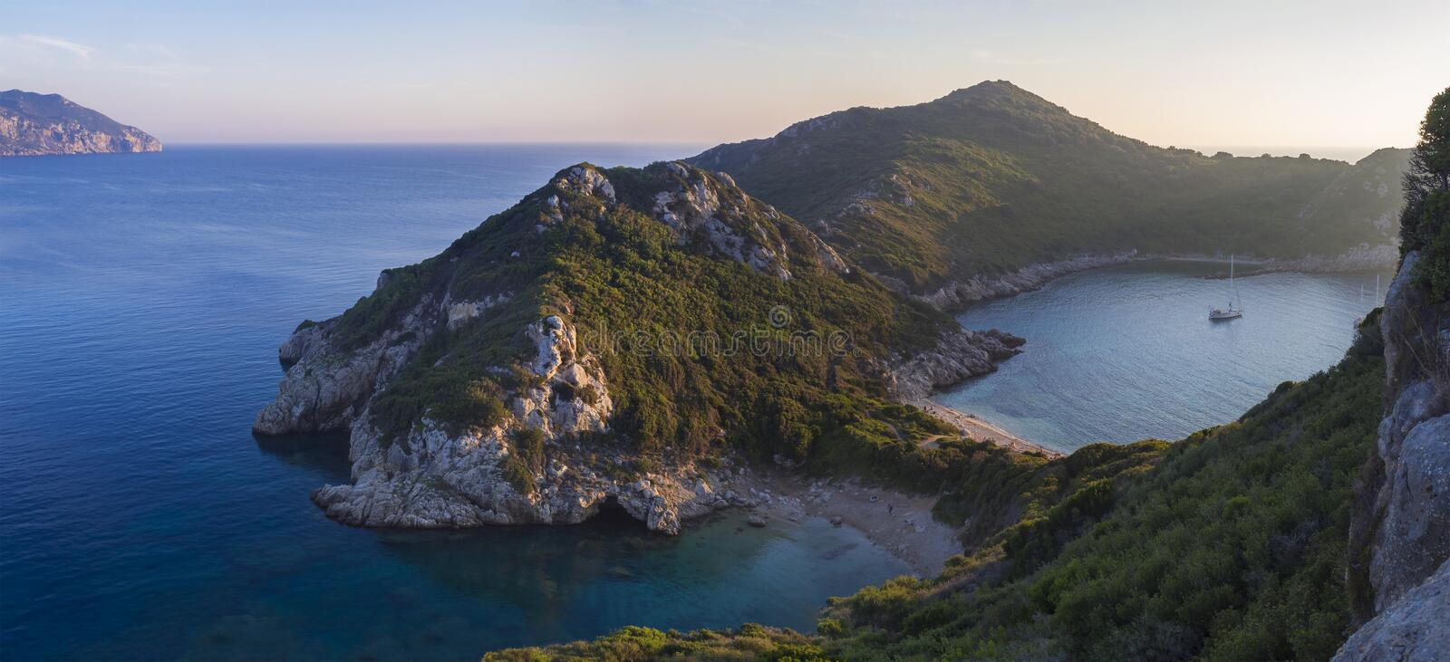 Panoramic view of beautiful famous double beach Porto Timoniand bay in Afionas from the view point on the path. Sunset golden pink. Corfu, Greece, Porto Timoni royalty free stock photography