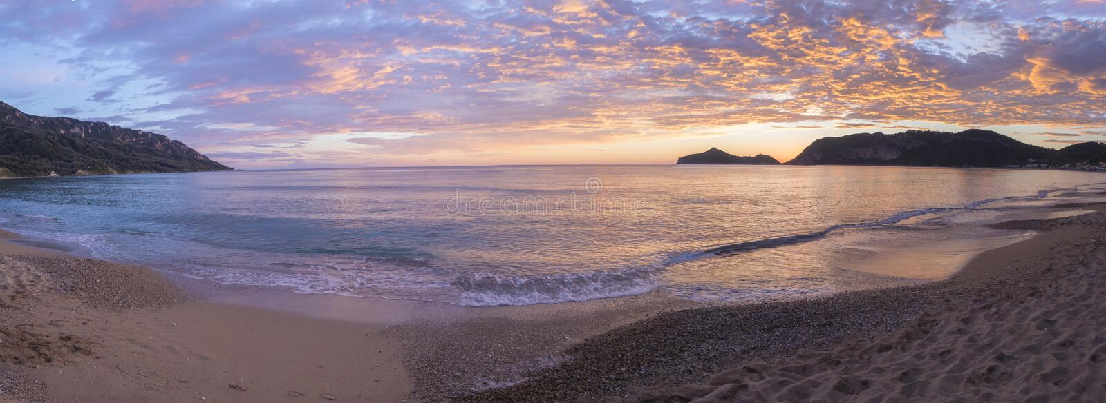 Panoramic view on beautiful pastel pink orange and golden sunset clouds and waves at sea shore Agios Georgios Pagon beach at Corfu stock photo