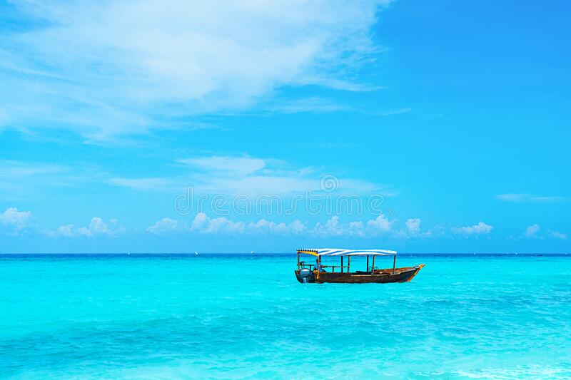 Panoramic view of a beautiful sunny day on sandy beach and fishing boat on Zanzibar. royalty free stock photo