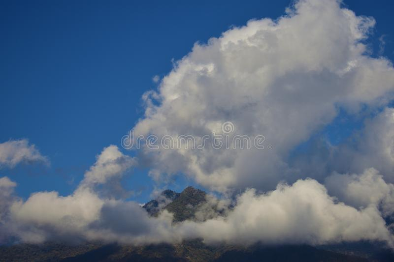 a panoramic view of the Bhutan Mountain in Bhutan capped by big white clouds stock photography