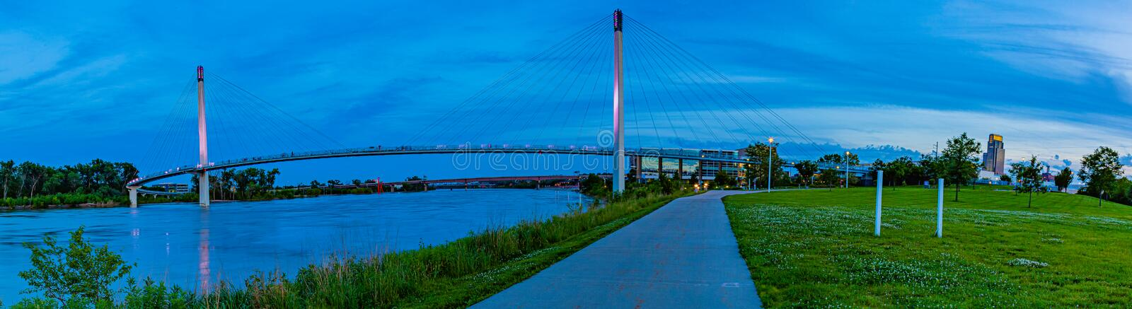 Panoramic view blue hour reflection on Bob Kerrey pedestrian bridge Omaha. Blue hour post Sunset reflections  on Bob Kerrey pedestrian foot bridge over Missouri royalty free stock images