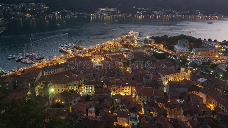 Panoramic view of Bokotsky Bay at sunset with evening lights on. Panoramic view of the old town of Kotor from the mountain at sunset with the evening lights royalty free stock photo
