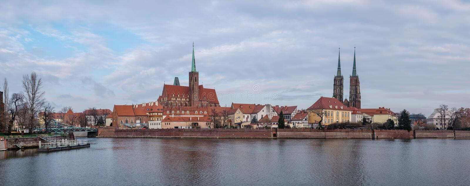 Panoramic view of the Cathedral of St. John the Baptist reflected in Oder river at cold foggy day. Ostrow Tumski district. Wroclaw. Poland stock images