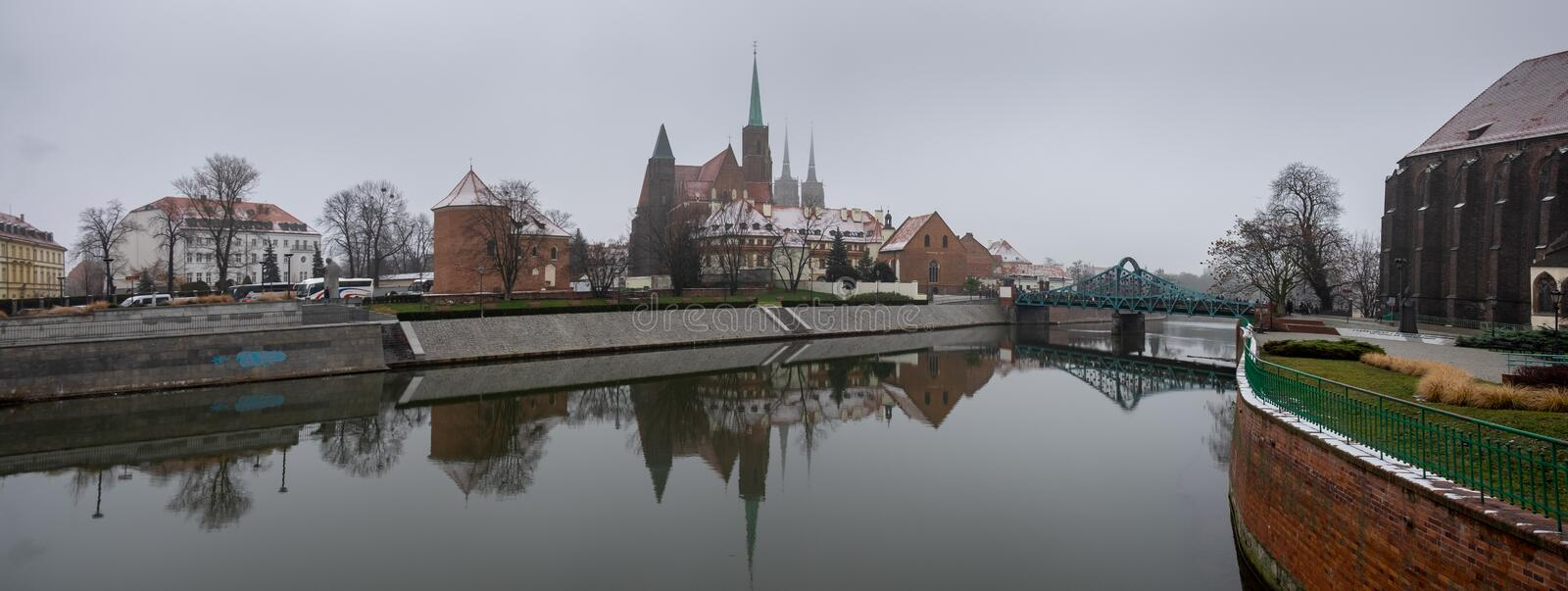 Panoramic view of the Cathedral of St. John the Baptist reflected in Oder river at cold snowy day. Ostrow Tumski district. Wroclaw. Poland stock image