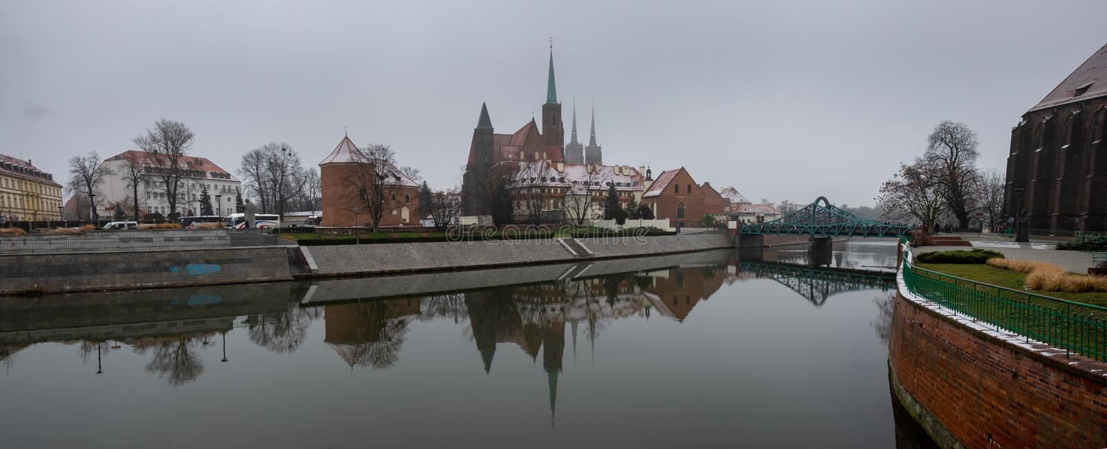 Panoramic view of the Cathedral of St. John the Baptist reflected in Oder river at cold snowy day. Ostrow Tumski district. Wroclaw. Poland royalty free stock images