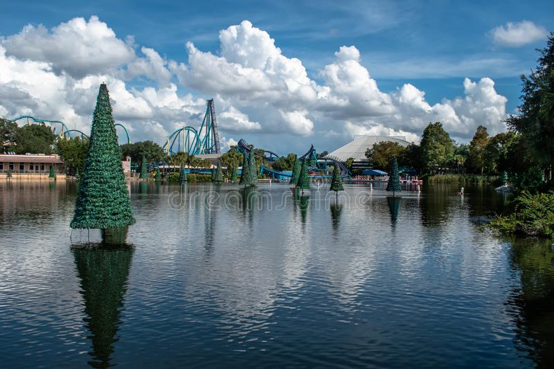 Panoramic view of Christmas trees on blue lake and rollercoaster at Seaworld 2. stock photography