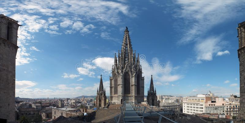 Panoramic view of the city from barcelona cathedral roof with the gothic tower and blue sky royalty free stock photo