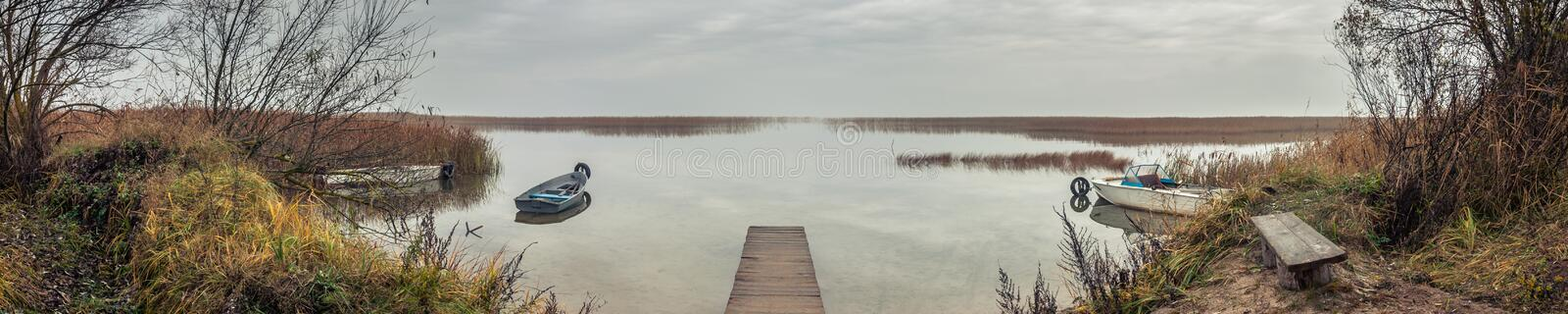 panoramic view from the coast to the lake bay with a wooden pier and boats in the autumn twilight in cloudy weather royalty free stock image