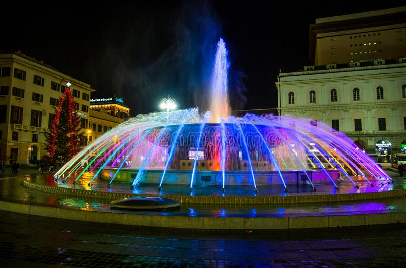 Panoramic view of the colorful fountain of De Ferrari square by night in Genoa, the heart of the city, Italy. Panoramic view of the colorful fountain of De royalty free stock photos