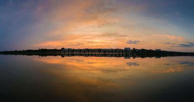 Panoramic view of colorful sunset clouds symmetric reflected on the lake surface. Idyllic summer evening, natural scene near a stock image