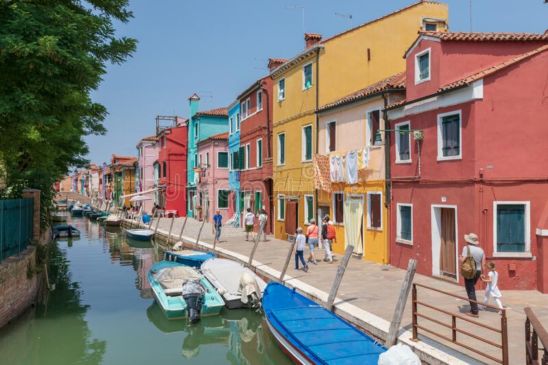 Panoramic view of coloured homes and water canal with boats in Burano stock images