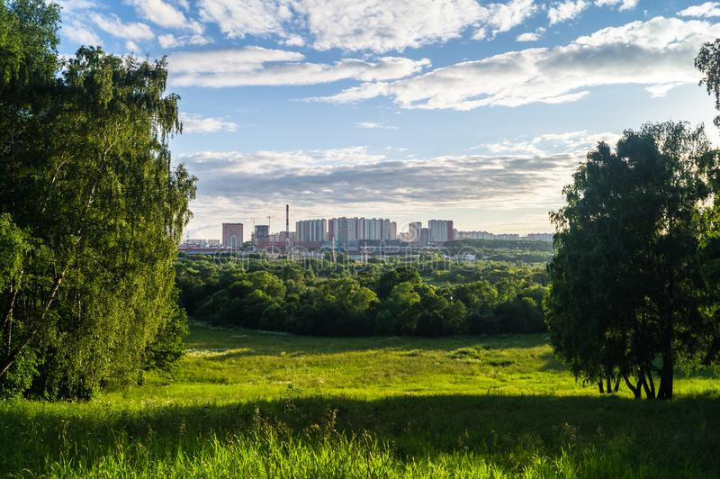 Panoramic view of the contemporary urban district from a picturesque untouched countryside hill. Invisible border between city and. Surrounding pristine nature royalty free stock image