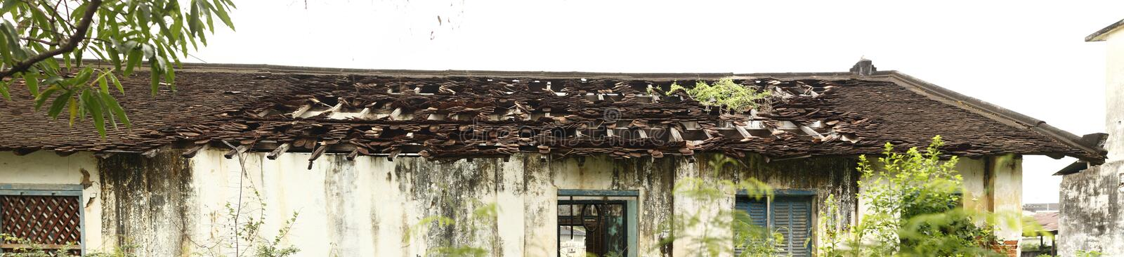 Panoramic view of a cracked, eroded and collapsed roof of an old home or shop in Laos stock photo
