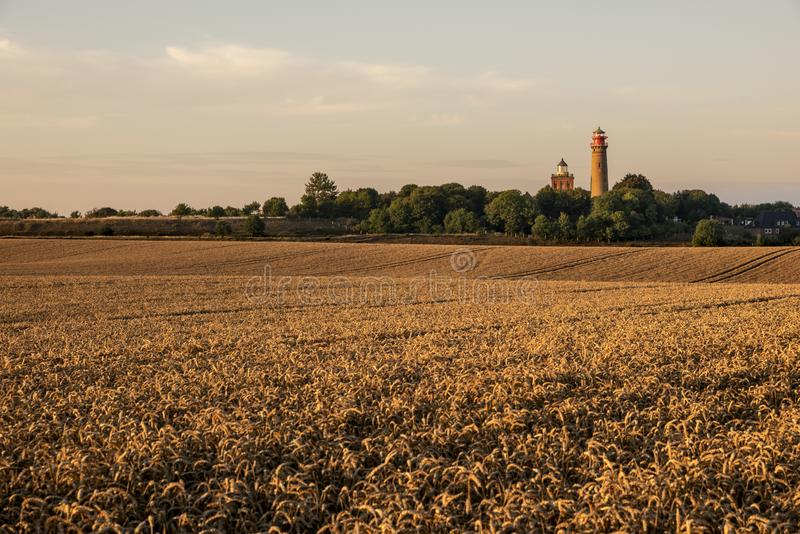 Panoramic view of cultivated fields at sunset with lighthouses in background. royalty free stock images