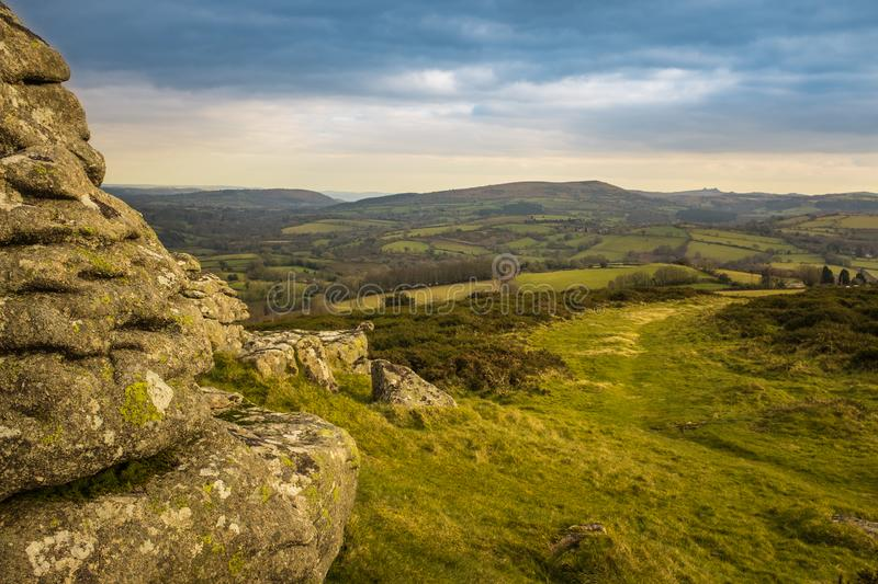 A panoramic view of Dartmoor National Park from Watern Tor, the green landscape leads into the distance. An overcast sky stock image