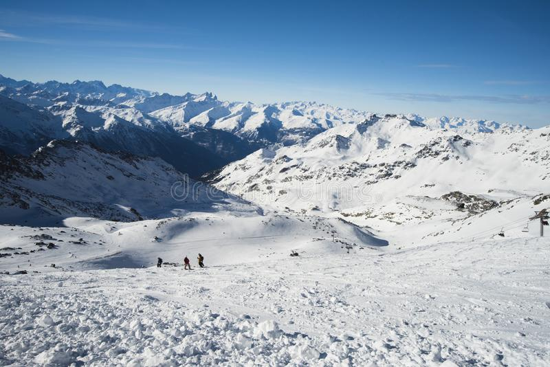 Panoramic view down snow covered valley in alpine mountain range royalty free stock images