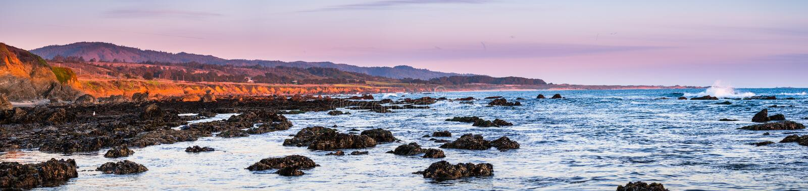 Panoramic view of the dramatic Pacific Ocean coastline at sunset, during low tide, Santa Cruz mountains in the background; San stock photo