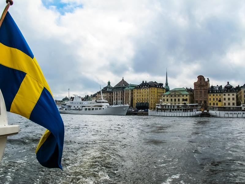 Panoramic view from the excursion boat with the flag of Sweden on tourist boats and waterfront houses in Gamla Stan. Stockholm. Sweden stock image
