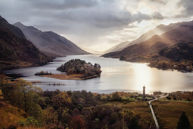 View with famous Scottish lake Loch Shiel with Glenfinnan monument on sunset. Panoramic view with famous Scottish lake Loch Shiel with Glenfinnan monument and stock photography