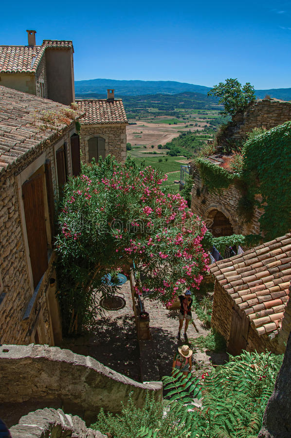 Panoramic view of fields and hills of Provence, stone houses and flowering trees in Gordes. stock images