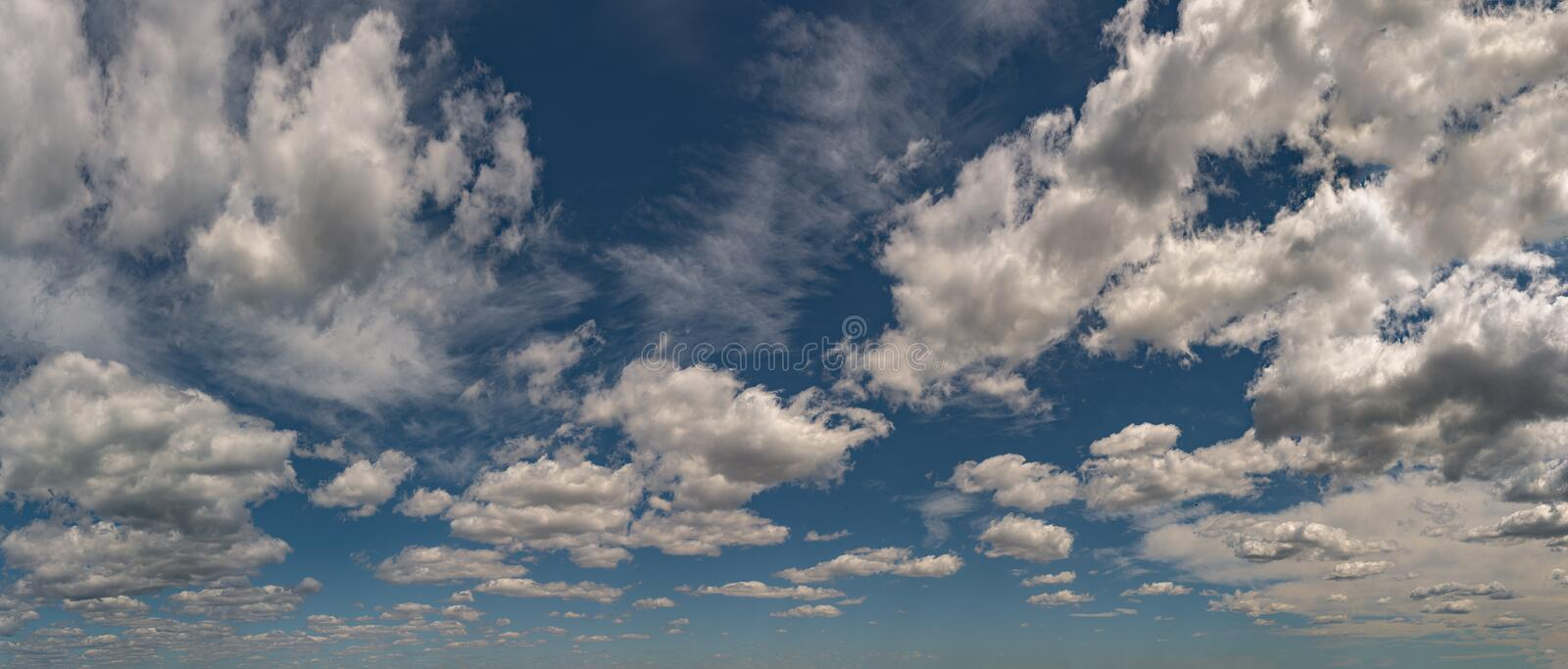 Fluffy gray and white cirrus clouds above horizon royalty free stock images