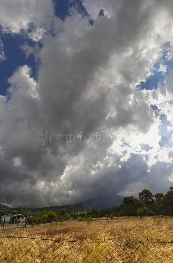 Panoramic view of Giant Cumulus clouds before the approaching summer storm in a village on the Greek island of Evia royalty free stock images