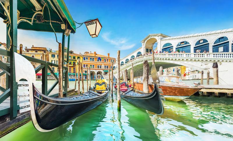 Panoramic view of Gondolas and boat at their moorings against famous Rialto Bridge at Grand Canal in Venice, Italy, Europe royalty free stock photography