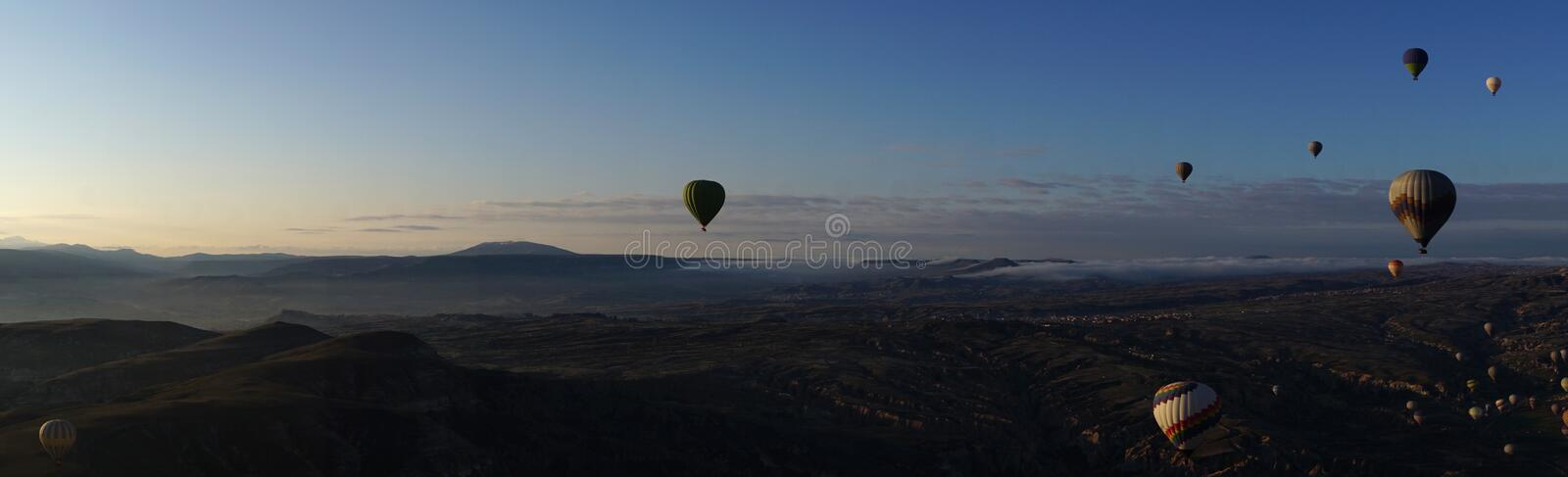 Panoramic view of Goreme beautiful landscape with hot air balloon floating in the sky. In the morning stock photography