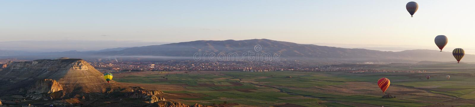 Panoramic view of Goreme beautiful landscape with hot air balloon floating in the sky. In the morning royalty free stock photos