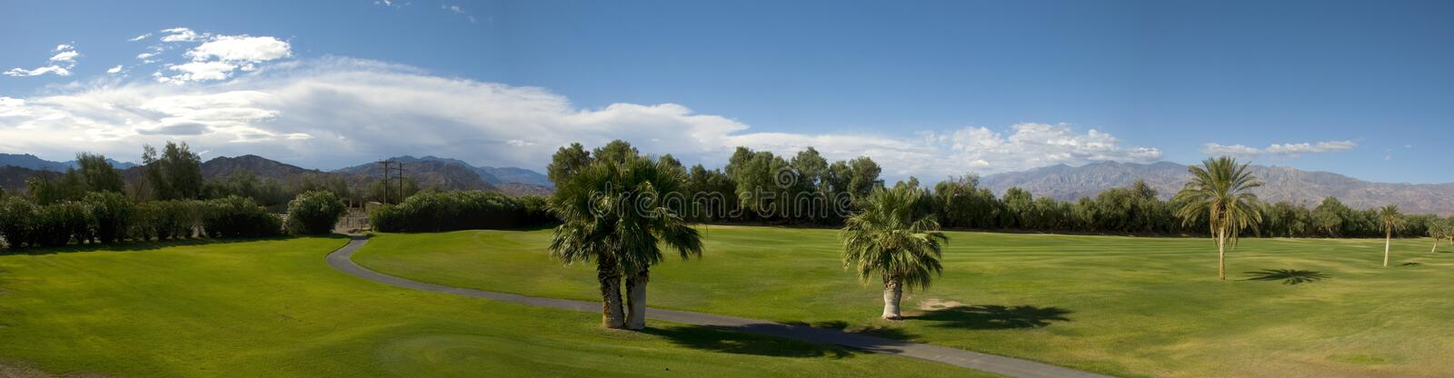 Panoramic view of green golf course in death valley stock photos