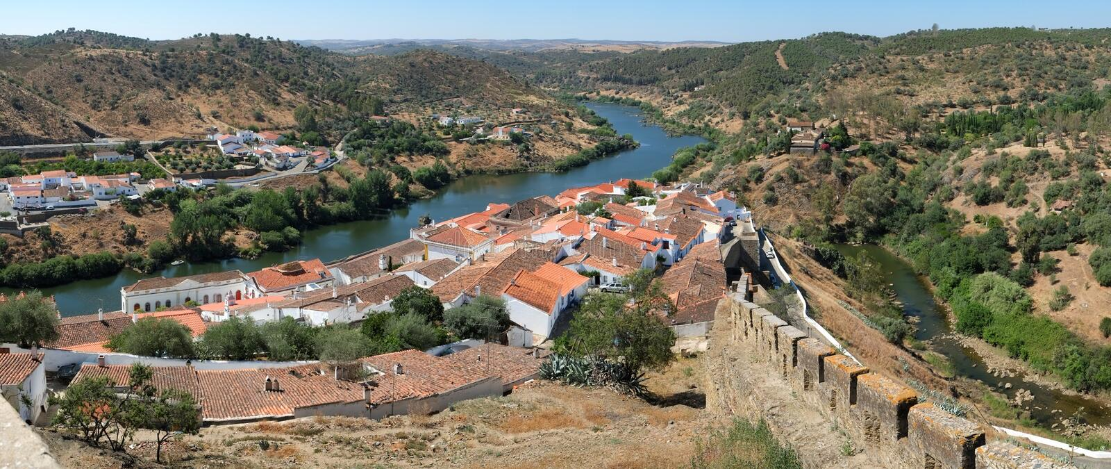 Panoramic view of Guadiana river bend and residential houses of Mertola city on the ripe. Portugal. Panoramic view of Guadiana river bend and residential houses stock photo