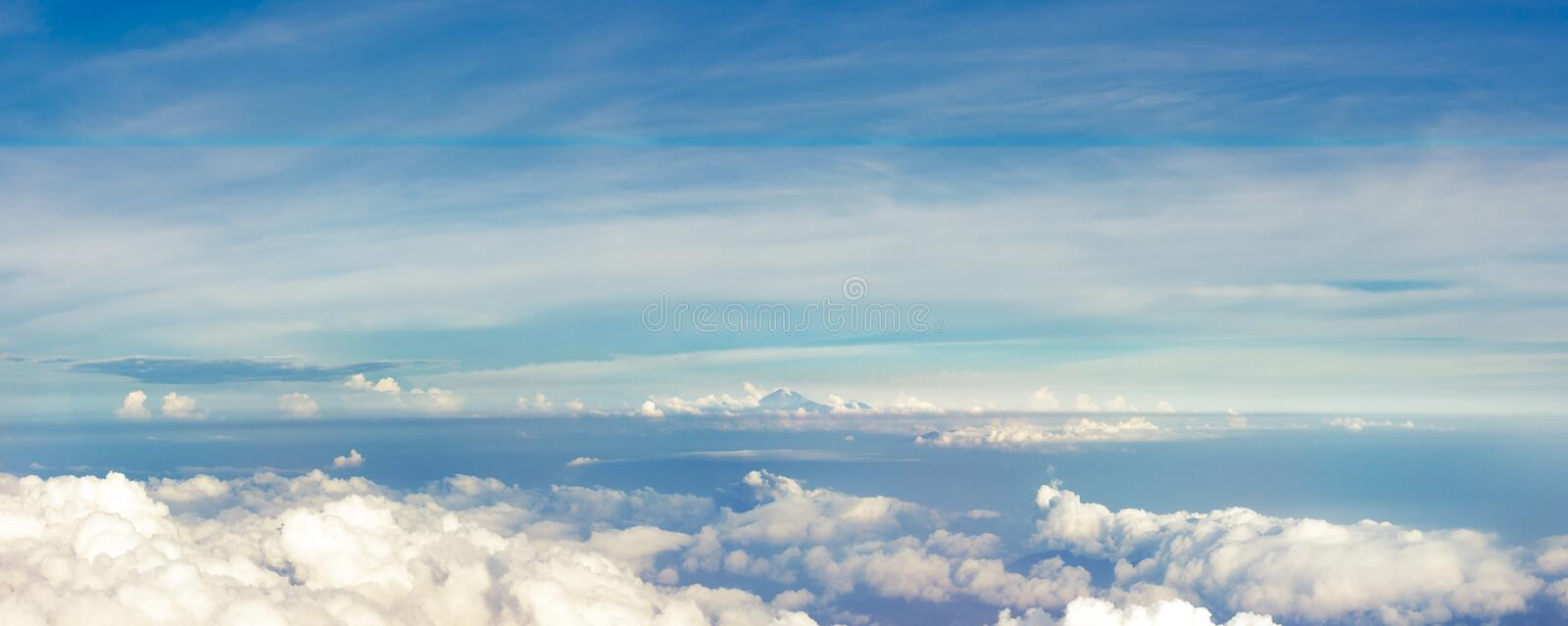 Panoramic view from a height above the clouds. Panoramic view of the horizon with volcano Rinjani afar stock image
