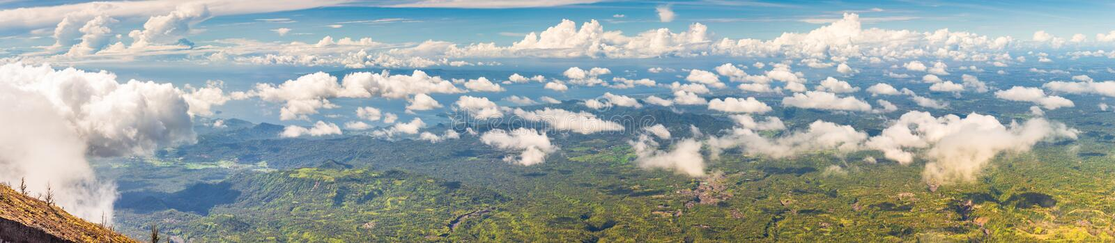 Panoramic view from a high green hill above the clouds to the sea, islands, rice terraces, fields and forests in indonesia, Agung. Panoramic view from a high royalty free stock photo
