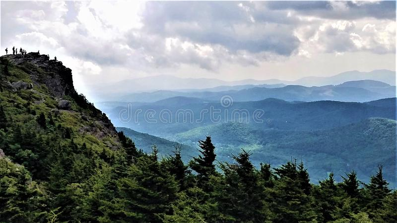 Panoramic view for hikers on Grandfather Mountain. Adventurous hikers brave an approaching storm to stand on top of Grandfather Mt. near Asheville, NC. Sun rays stock photos