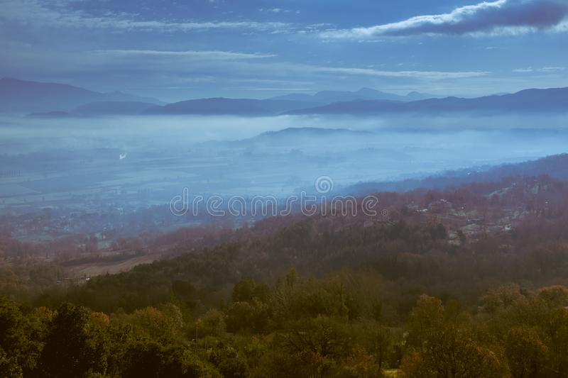 Panoramic view from a hill in the evening with low clouds over the valley royalty free stock photo