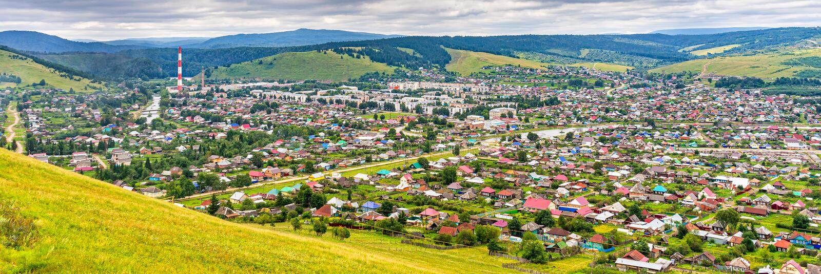 Panoramic view from hill to plain with small town in summer cloudy day. Picturesque urban landscape with many colorful houses. Sim royalty free stock photography